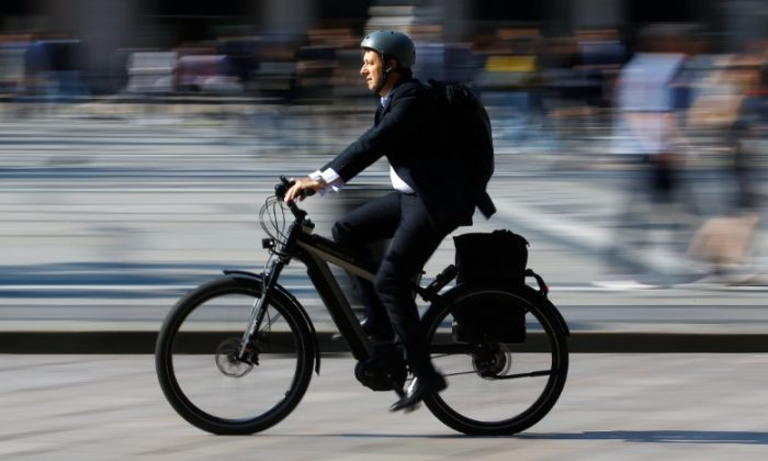 A man rides an electric bicycle, also known as an e-bike, in downtown Milan, Italy on May 18, 2018. (Stefano Rellandini/Reuters)
