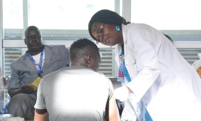 A medical officer offers consultation to a returnee from Niger upon arrival at the Yaounde Nsimalen International Airport in Cameroon on May 9, 2018. (IOM/Serena Pescatore)