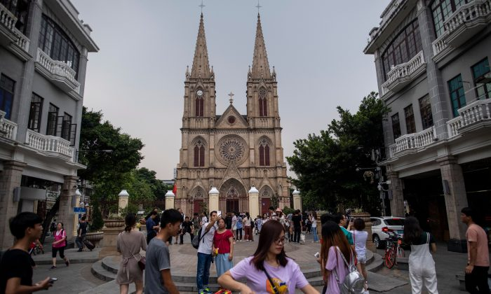 Chinese tourists in front of the  Sacred Heart Cathedral, or Shishi Catholic Church, in Guangzhou, in Guangdong Province, on  Sept. 22, 2018. China and the Vatican will push to improve bilateral ties after the two sides signed a 'provisional' agreement on the appointment of bishops, the Chinese foreign ministry said on Sept. 22, 2018. (JOHANNES EISELE/AFP/Getty Images)