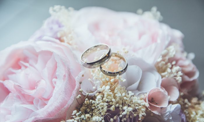 Two rings sit on a floral bouquet. (Beatriz Perez-Moya/Unsplash)