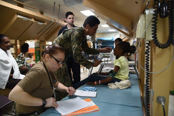Personnel provide medical care aboard the U.S. hospital ship USNS.