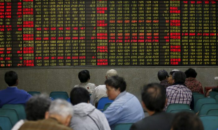 Investors look at an electronic board showing stock information at a brokerage house in Shanghai, China on April 21, 2016. (Aly Song/Reuters)