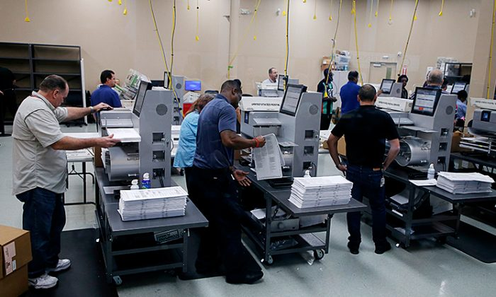 Elections staff load ballots into machines as recounting begins at the Broward County Supervisor of Elections Office in Lauderhill, Florida on Nov. 11, 2018. (Joe Skipper/Getty Images)