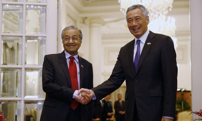 Malaysia's Prime Minister Mahathir Mohamad (R) shakes hands with Singaporean counterpart Lee Hsien Loong during a meeting at the Presidential Palace on the sidelines of the 33rd Association of Southeast Asian Nations (ASEAN) summit in Singapore on Nov. 12, 2018. (FELINE LIM/AFP/Getty Images)