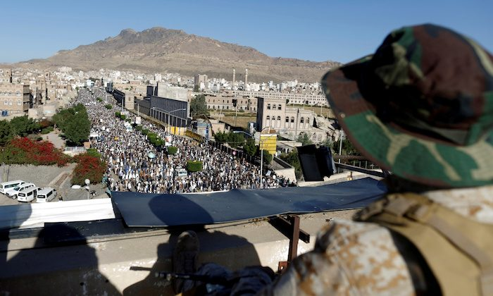 A Houthi militant sits guard on the roof of a building overlooking fellow Houthis rallying to denounce the rapid devaluation of the Yemeni Rial in Sanaa, Yemen Oct. 5, 2018. (Reuters/Khaled Abdullah)