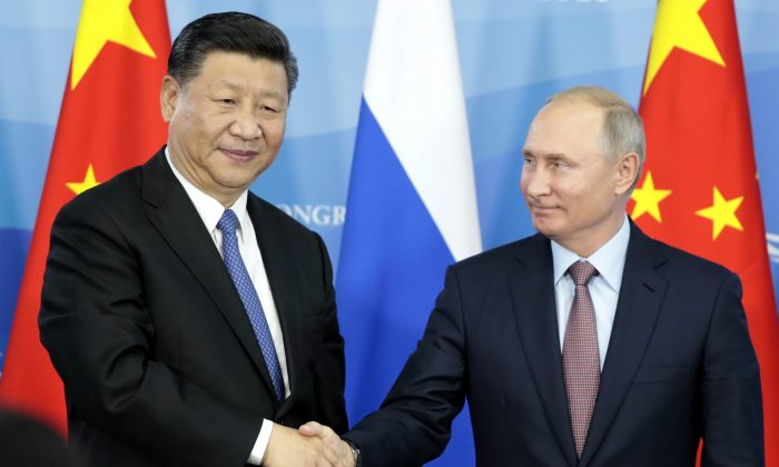 Russia's President Vladimir Putin (R) shakes hands with his China's counterpart Xi Jinping during a signing ceremony following the Russian-Chinese talks on the sidelines of the Eastern Economic Forum in Vladivostok on Sept. 11, 2018. (SERGEI CHIRIKOV/AFP/Getty Images)