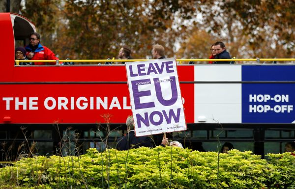 A pro-Brexit campaigner holds a placard as a tourist bus passes by