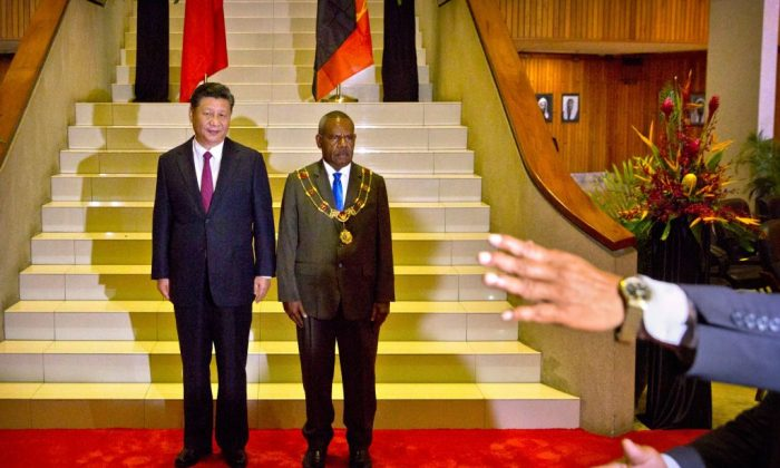 An official gestures as China's President Xi Jinping (L) and Papua New Guinea's Governor General Bob Dadae pose for photos before a meeting at Parliament House in Port Moresby on Nov. 16, 2018, ahead of the Asia-Pacific Economic Cooperation (APEC) Summit. (Mark Schiefelbein/AFP/Getty Images)