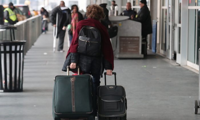 A woman carries her luggage to departing flights entrance at LaGuardia Airport in New York, on Nov. 20, 2018. (Shannon Stapleton/Reuters)