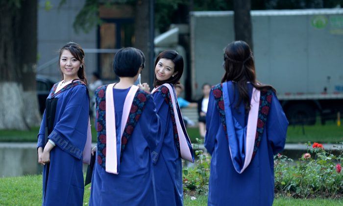 A group of students pose for photographs at a university in Beijing on June 8, 2015. Despite a boom in student numbers in recent years, many graduates from second and third-tier institutions face considerable employment uncertainty in an economy largely fuelled by a blue-collar workforce.    AFP PHOTO / WANG ZHAO        (Photo credit should read WANG ZHAO/AFP/Getty Images)