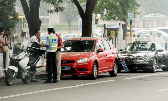 A Chinese policeman tries to resolve a traffic dispute between the driver of a luxury Porsche car and another after an accident in Beijing on Aug. 9, 2011. (Mark Ralston/AFP/Getty Images)