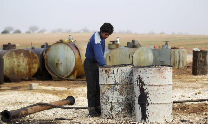 A youth works at a makeshift oil refinery site in Marchmarin town, southern countryside of Idlib, Syria on Dec. 16, 2015. (Khalil Ashawi/Reuters)