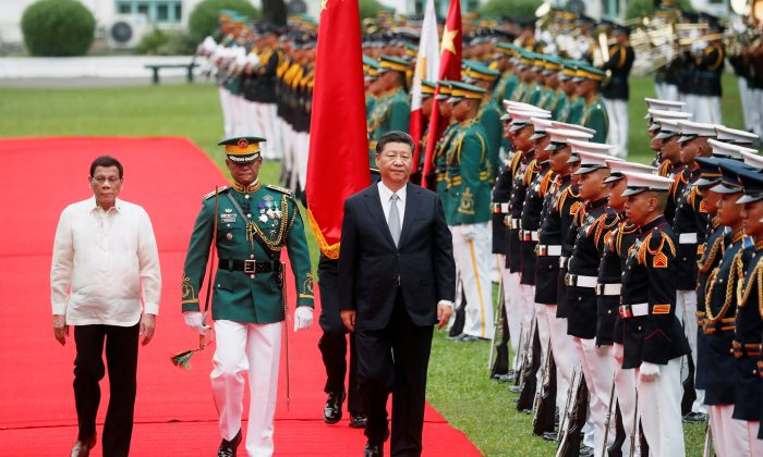 Visiting Chinese leader Xi Jinping with Philippine President Rodrigo Duterte troop the line before their one-on-one meeting at the Malacanang presidential palace in Manila on Nov. 20, 2018. (Erik De Castro/Reuters)