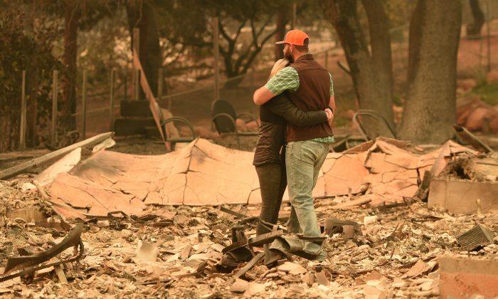 A couple embrace while looking over the remains of their burned residence after the Camp fire in Paradise, Calif., on Nov. 12, 2018. (Josh Edelson/AFP/Getty Images)
