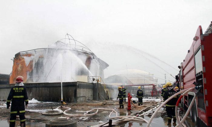 Firefighters douse a chemical tank after a blast at a plant producing paraxylene—a chemical commonly known as PX—in Zhangzhou, Fujian Province, China on April 9, 2015. Almost 30,000 people living near a Chinese chemical plant where a huge fire blazed for a total of nearly 50 hours were evacuated before the flames were finally extinguished. (STR/AFP/Getty Images)