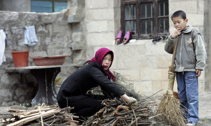 A woman farmer tieing a bunch of firewood as her son watches outside their home in Hutou village on Pingtan island. (GOH CHAI HIN/AFP/Getty Images)