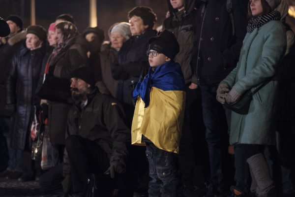 A boy listens as activists and religious leaders speak during a ceremony in Kharkiv, Ukraine.
