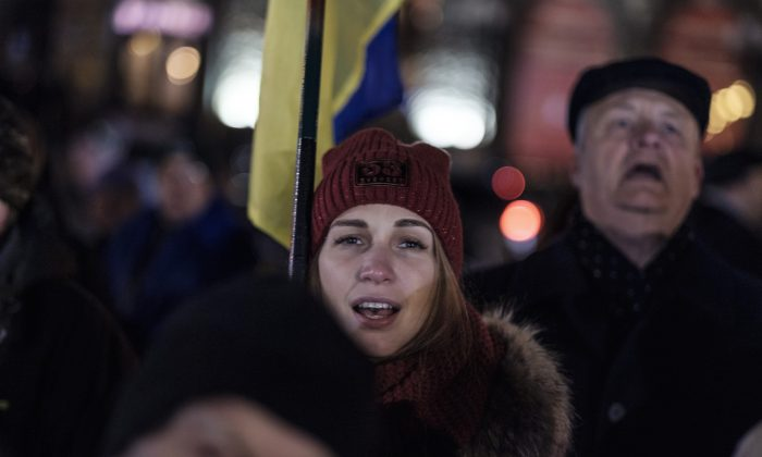 A woman sings along to Ukraine's national anthem at an event in the eastern city of Kharkiv on Nov. 21, 2018, commemorating five years since the Nov. 2013 protests that resulted in the ouster of President Viktor Yanukovych. (Chris Collison/Special to The Epoch Times)
