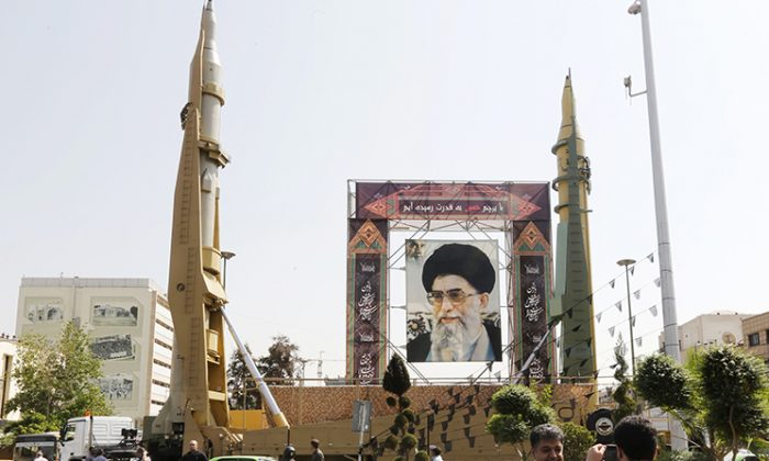 Iranians walk past Sejjil (L) and Qadr-H medium range ballistic missiles displayed next to a portrait of Iranian Supreme Leader Ayatollah Ali Khamenei, on Sept. 25, 2017, on Baharestan square in Tehran. (Atta Kenare/AFP/Getty Images)