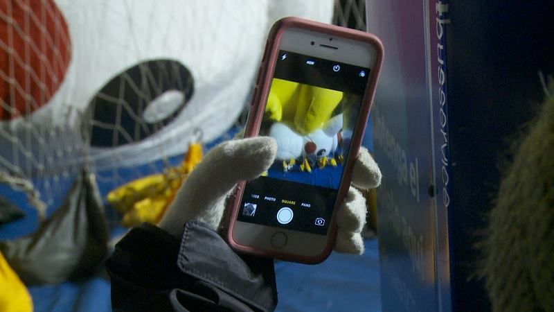 Spectator takes picture of Pikachu balloon at the Macy's Thanksgiving Day Parade.