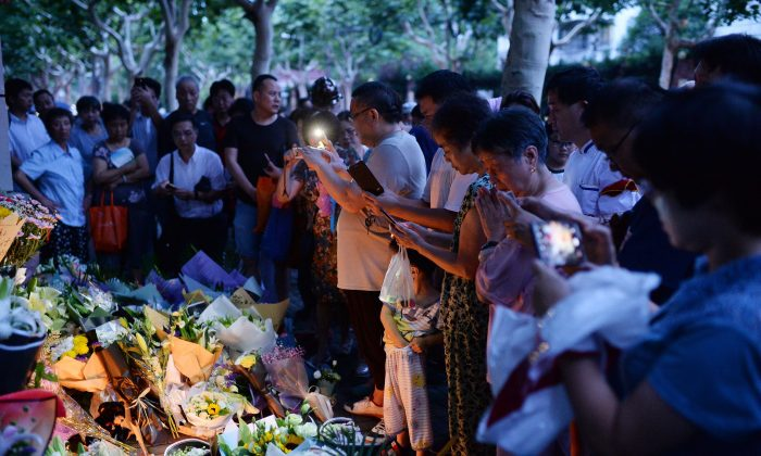 Children and adults pray during a candle-light vigil at the site of a knife attack which left two children dead in Shanghai, China on June 28, 2018. A man stabbed two boys to death outside a Shanghai elementary school on June 28, police said, one of the latest in a series of similar attacks in China in recent years. (AFP/Getty Images)