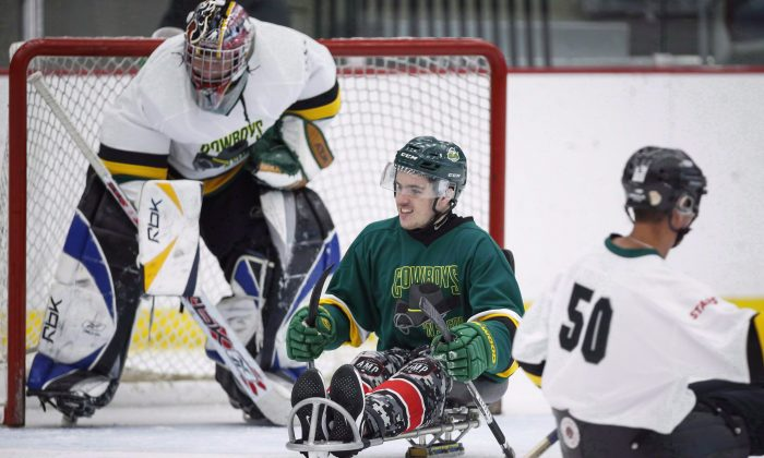 Humboldt Broncos bus crash survivor Ryan Straschnitzki (2-L) plays in a fundraising sledge hockey game in Calgary, Alta.,on Sept. 15, 2018. (The Canadian Press/Jeff McIntosh)