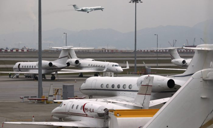 A business jet takes off as others are parked at the Hong Kong Airport on Feb. 17, 2012. (Bobby Yip/Reuters)