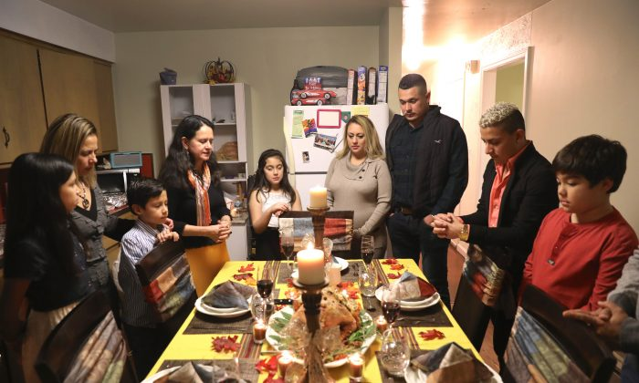 Friends and families pray before Thanksgiving dinner in Stamford, Conn., on Nov. 24, 2016. (John Moore/Getty Images)