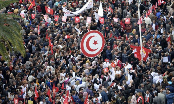 Tunisian protesters wave national flags and chant slogans during a civil servants general strike after the failure of negotiations with the government on salary increases in the capital Tunis on Nov. 22, 2018. FETHI BELAID/AFP/Getty Images)