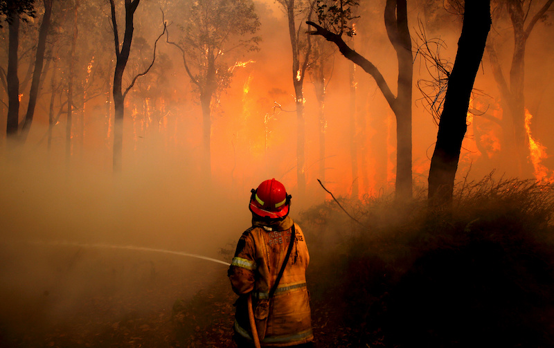 Firefighter sprays water on bushfire
