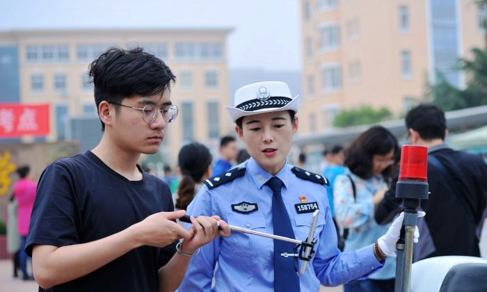 "A traffic police officer (R) uses a smartphone to report during a live broadcasting outside a school at the first day of the 2018 college entrance exam of China, or the ""Gaokao"", in Qingdao in China's eastern Shandong province on June 7, 2018. (AFP/Getty Images)"