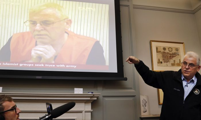 British investigator, Peter Humphrey, addresses the media in front of a screen showing him in a Chinese state TV interview, during a press conference in London, on Nov. 23, 2018. (AP Photo/Frank Augstein)