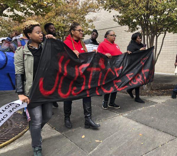 Protestors carry a sign