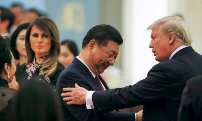US President Donald Trump (R) talks to China's President Xi Jinping, as US First Lady Melania Trump (L)  watches, during a state dinner at the Great Hall of the People in Beijing on November 9, 2017. 