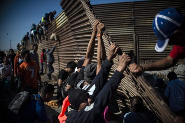 A group of Central American migrants climb the border fence between Mexico and the United States as others try to bring it down, near El Chaparral border crossing, in Tijuana, Baja California State, Mexico