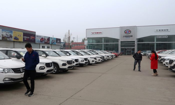 Dealers and customers are seen next to cars at a SAIC-GM-Wuling Baojun dealership in Pingdingshan, Henan Province, China on Nov. 15, 2018. (Yilei Sun/Reuters)