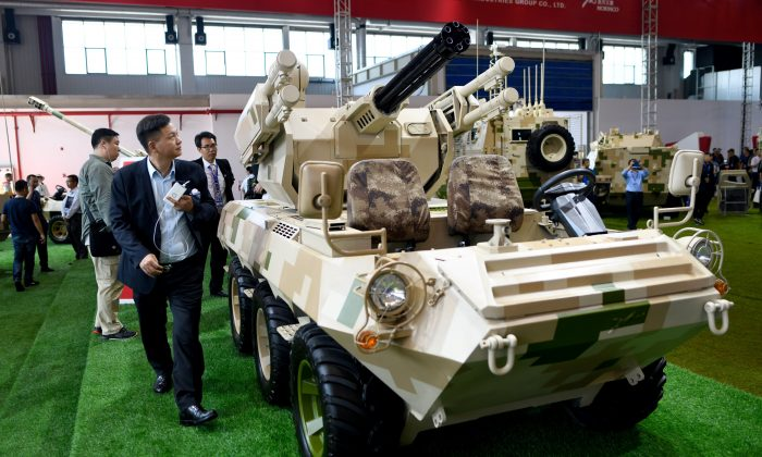 """Visitors look at a """"wheeled combat vehicle"""" on display at the 2018 Airshow China in Zhuhai, China, on Nov. 7, 2018.  (WANG ZHAO/AFP/Getty Images)"""