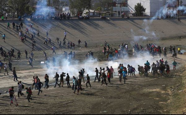 Migrants run from tear gas, thrown by the U.S. border patrol,
