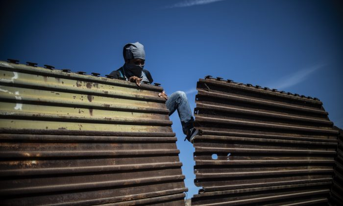 A Central American migrant tries to bring down part of the border fence between Mexico and the United States, near El Chaparral border crossing, in Tijuana, Baja California State, Mexico, on Nov 25, 2018. (Pedro Pardo/AFP/Getty Images)