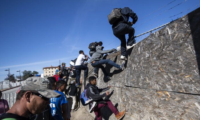 A group of Central American migrants -mostly from Honduras- get over a fence as they try to reach the US-Mexico border near the El Chaparral border crossing in Tijuana, Baja California State, Mexico, on Nov. 25, 2018. (Pedro Pardo/AFP/Getty Images)