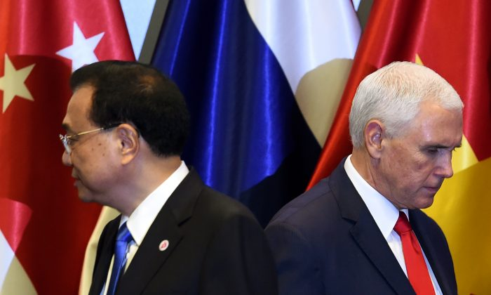 U.S. Vice President Mike Pence (R) and Chinese Premier Li Keqiang leave the stage after posing for a group photo before the start of the 13th East Asia summit plenary session on the sidelines of the 33rd Association of Southeast Asian Nations (ASEAN) summit in Singapore on Nov. 15, 2018. (ROSLAN RAHMAN/AFP/Getty Images)