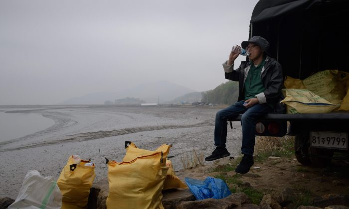 A North Korean defector activist sits with bags of bottles containing rice, money, and USB sticks, on Ganghwa island, west of Seoul, on May 1, 2018. North Korean defectors send the supplies floating towards their homeland. (Ed Jones/AFP/Getty Images)