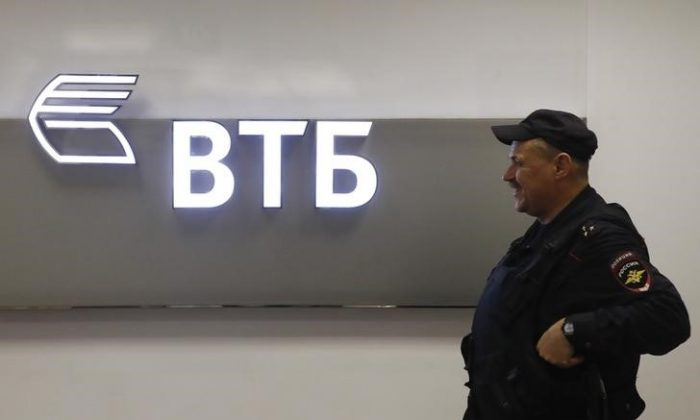 "A police officer stands guard near a sign with the logo of the Russian lender VTB at the Moscow International Business Centre also known as ""Moskva-City"" in Moscow, Russia on Nov. 21, 2017. (Maxim Shemetov/Reuters)"