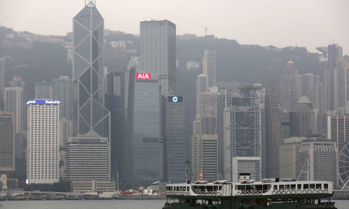 A ferry sails at Victoria Harbour in front of the financial central district in Hong Kong on Feb. 17, 2016. (Bobby Yip/Reuters)