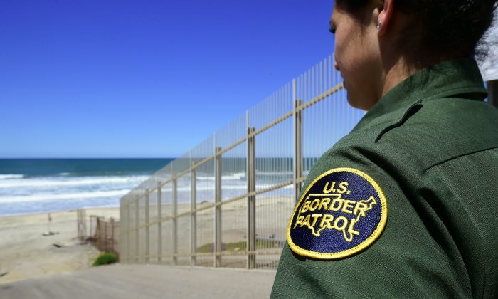 A U.S. Customs and Border Protection agent looks toward the ocean from within the Border Infrastructure System, a no man's land area between the wall and fence separating California from Mexico on April 17, 2018 in San Diego, California. The way we talk about immigration affects public opinion and government policy. (FREDERIC J. BROWN/AFP/Getty Images)