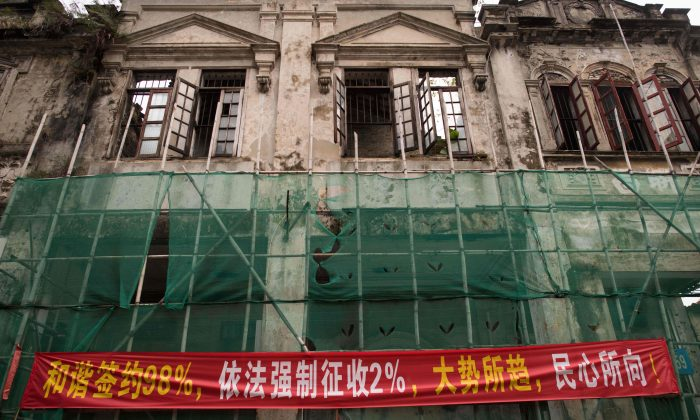 "In this picture taken on May 28, 2018, a banner that reads ""98 percent of people have signed contracts in a pleasing way, 2 percent of peoples houses have been forced-collected according to law, its the trend of the time and coinciding with the popular will"" is seen on a building in Chikan village in Kaiping. (NICOLAS ASFOURI/AFP/Getty Images)"