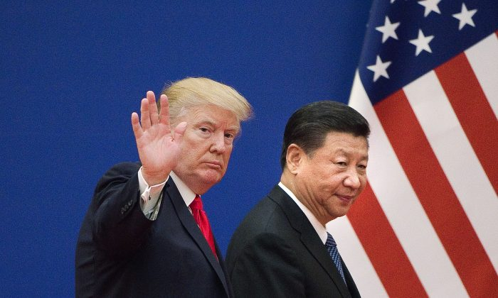 U.S. President Donald Trump (L) and Chinese leader Xi Jinping leave a business leaders event at the Great Hall of the People in Beijing on November 9, 2017.