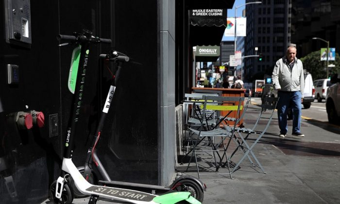 Bird and Lime scooters sit parked in front of a building in San Francisco, Cali, on April 17, 2018 (Justin Sullivan/Getty Images)