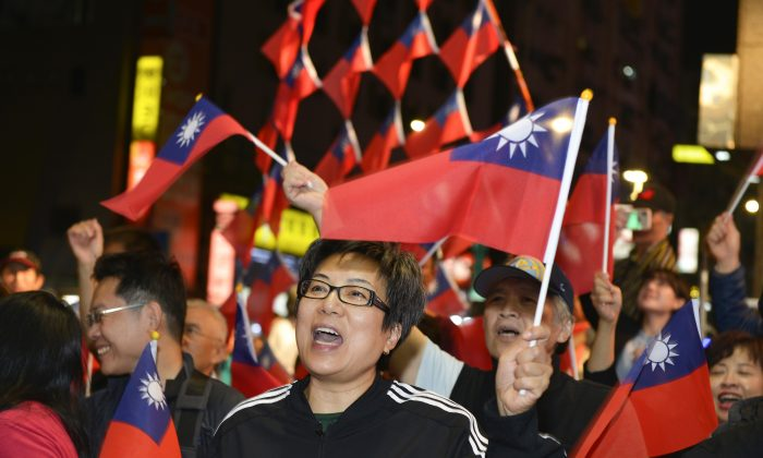 Supporters of mayoral candidate Ting Shou-chung from the Kuomintang (KMT) party wave national flags at Ting's campaign headquarters during local elections in Taipei, on Nov. 24, 2018. (Chris Stowers/AFP/Getty Images)