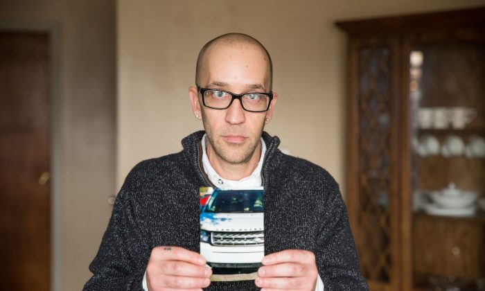 Tyson Timbs holds a picture of the Land Rover confiscated by the state of Indiana as part of a conviction for selling drugs. (Institute of Justice)